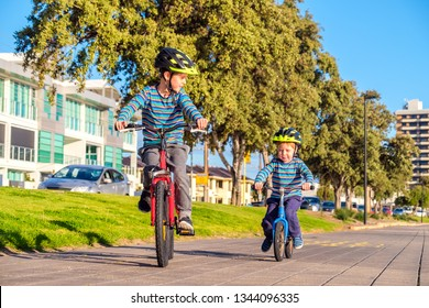 Children riding their bicycles along lake at Glenelg, South Australia