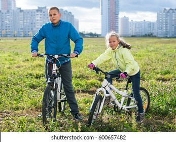 Children riding their bikes on a green field in the city