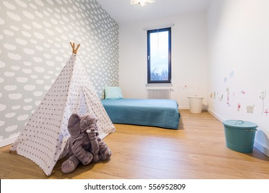 Children room with blue bed by the wall and small tipi tent in the middle. On the wall wallpaper with pictures