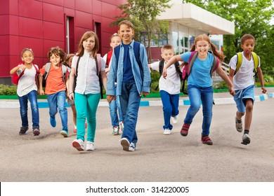 Children with rucksacks near school walking