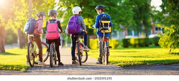 Kinder mit Rucksacksack fahren im Park in der Nähe der Schule. Schüler mit Rucksäcken im Freien