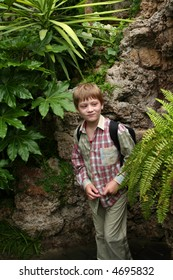 Children with rucksacks visiting big green greenhouse