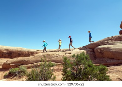 Children run along the red rocks on background blue sky in the Arches National Park, Utah