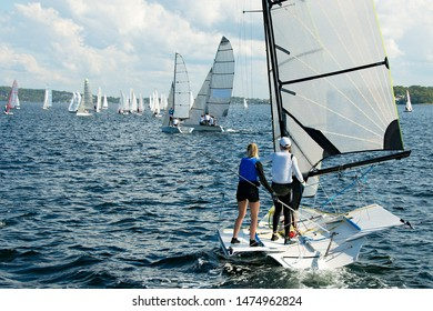Children Sailing small boat with a closeup stern view of one dinghy in the foreground with many other boats in the background at an inland lake regatta. Teamwork by junior sailors. Commercial Use.