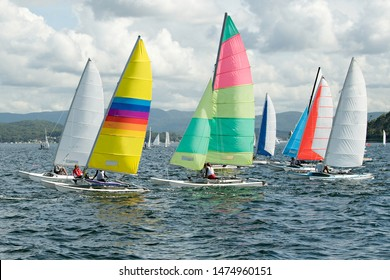 Children sailing in small boats and dinghies with colourful sails for fun and competition. Teamwork by junior sailors racing on saltwater Lake Macquarie. Photo for commercial use.