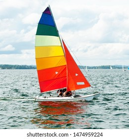 Children sailing in small colourful boats and dinghies for fun and competition. Teamwork by junior sailors racing on salt water Lake Macquarie. Photo for commercial use.