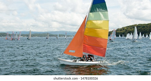 Children sailing in small colourful boats and dinghies for fun and in competition. Teamwork by junior sailors racing on saltwater with a catamaran closeup in the foreground at Lake Macquarie. Photo fo