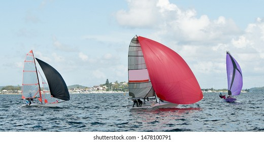 Children sailing in small colourful boats and dinghies for fun and in competition. Teamwork by junior sailors racing on saltwater Lake Macquarie. Photo for commercial use.