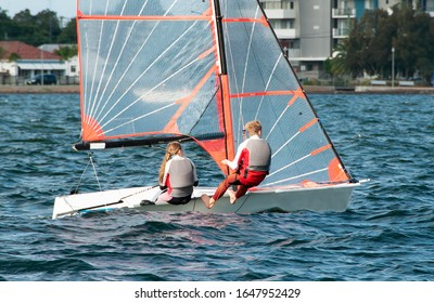 Children sailing in small colourful boats and dinghies for fun and in competition. Teamwork by junior sailors.  Lake Macquarie. Australia.
