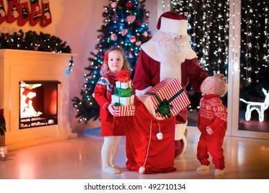 Children and Santa Claus at fireplace on Christmas eve. Family celebrating Xmas. Decorated living room with tree, gifts, fire place, candles. Winter evening at home for parents and kids.
