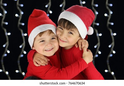 children with santa claus hats in a big hug with black background and lights