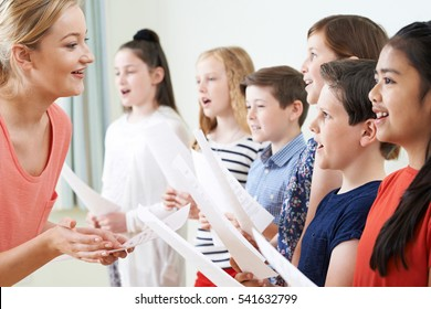 Children In School Choir Being Encouraged By Teacher