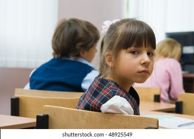 Children at school at a lesson. The thoughtful girl sits at a school desk