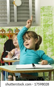 The children are in a school room.  The girl in front is raising her hand to answer a question.  Vertically framed shot.