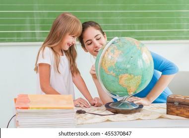 Children at school - teacher showing globe