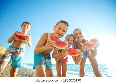 Children at sea. A group of children are eating a watermelon. High quality photo.