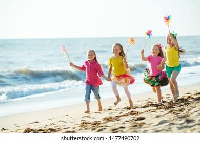 Children at sea. Little girls run on the sea on the waves.