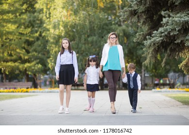 Children siblings and Mother holding hands going to school