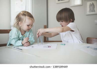 Children siblings paint at a table in a white kitchen in a real interior, brother and sister write next on paper
