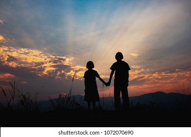 children silhouettes on summer meadow at sunset time