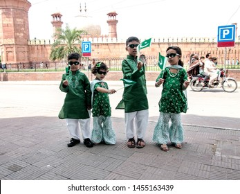Children sing national song and wave Pakistani flags,  children wearing green and white colors dress and held in hands Pakistani flags. city Lahore, province of Punjab Pakistan. dated 14/08/2017.