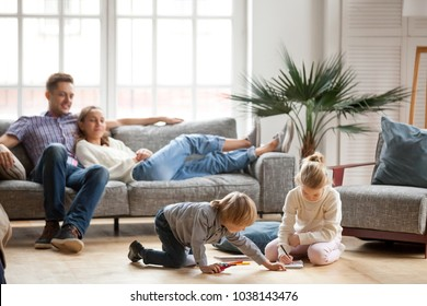Children sister and brother playing drawing together on floor while young parents relaxing at home on sofa, little boy girl having fun, friendship between siblings, family leisure time in living room
