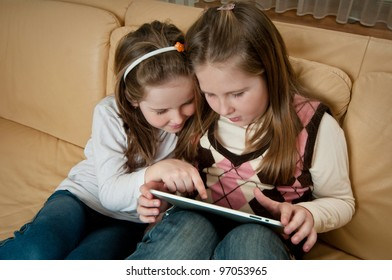 Children (sisters) playing with tablet at home on sofa