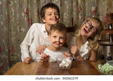 Children sit near chocolate fountain