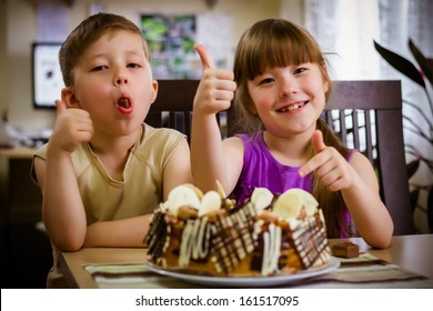 Children sit near a table and eat a cake