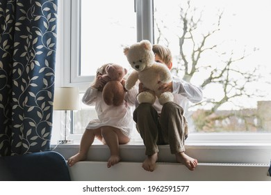 Children sit on the windowsill. A boy and a girl are playing. Teddy bear. Indoors. - Shutterstock ID 1962591577