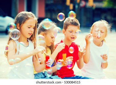 Children sit at playground and make soap bubbles for fun focus on girl