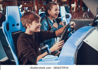 Children sit at slot machines and have fun. Cheerful sister cheering on brother who drives a toy car in a video game.
