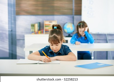 Children sitting at desk in primary school classroom, learning mathematics. Elementary age children.