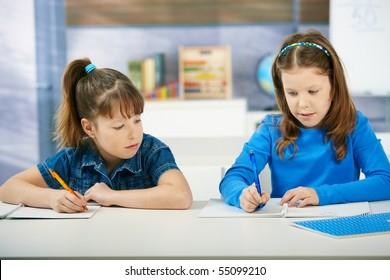 Children sitting at desk working together in primary school classroom.  Elementary age children.?