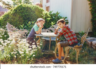 children are sitting in the garden at the table. bored kids in the yard near the house. The concept of idleness and apathy