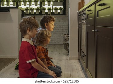 Children sitting near oven in the kitchen and waiting