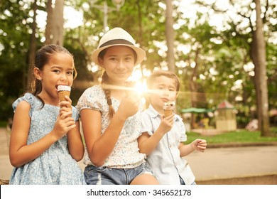 Children sitting on a bench and eating ice-creams