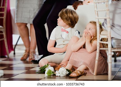 Children are sitting on the dancefloor by a table at a wedding. They are watching the bride and groom share their first dance.