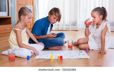 Children Sitting On Floor And Playing Board Game With Dice. Selective Focus