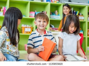 Children sitting on floor and reading tale book  in preschool library with teacher,Kindergarten school education concept