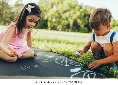 Children sitting on the green grass playing with colorful chalks. Happy two little kids drawing with chalks in the park. Two friends, boy and girl having fun on sunlight outdoors. Childhood