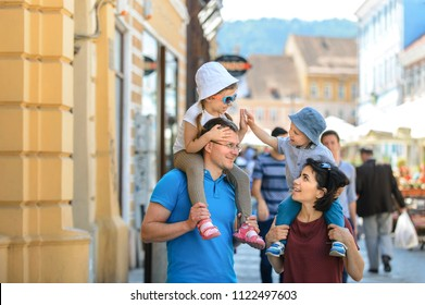 children sitting on parent's shoulders and having fun in street