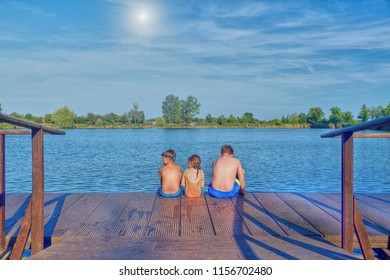 Children sitting on pier. Three children of different age - teenager boy, elementary age boy and preschool girl sitting on a wooden pier. Summer and childhood concept. Children on bench at the lake.