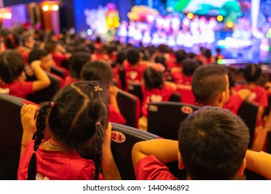 Children sitting on seats in the theater watching the performance