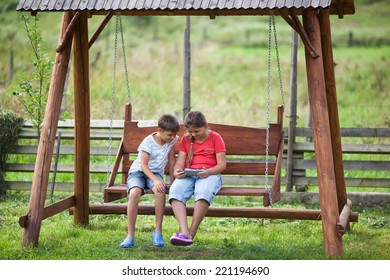 Children sitting on swing with digital tablet
