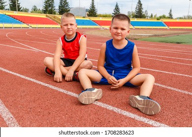 children sitting on the treadmill at the stadium. child after a run