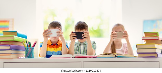 Children sitting in the room with smart phones. Pupils surfing at school