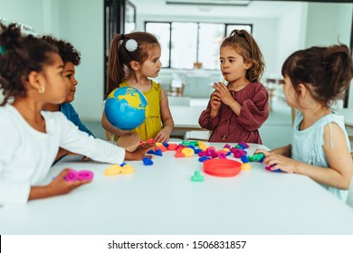 Children are sitting at the table in the kindergarten and playing with toys