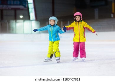 Children skating on indoor ice rink. Kids and family healthy winter sport. Boy and girl with ice skates. Active after school sports training for young child. Snow fun activity by cold weather.