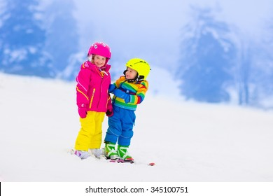 Children skiing in the mountains. Toddler kids in colorful suit and safety helmet learning to ski. Winter sport for family with young child. Kid ski lesson in alpine school. Snow fun for little skier.